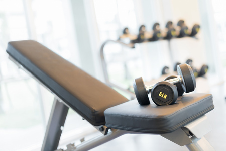 Two dumbbells on the exercise bench. Gym equipment.