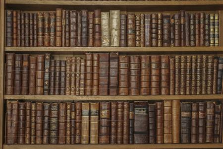 Photo pour Wooden bookshelves with antique leather books - image libre de droit