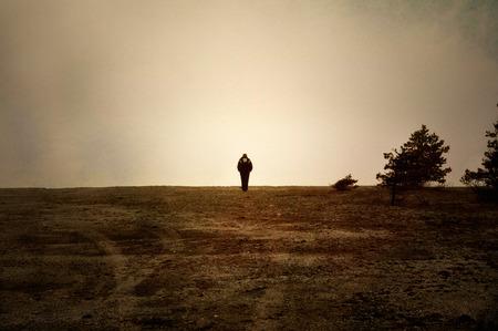 Foto de Image textured with soft sandstone of human walking alone on a moor. - Imagen libre de derechos