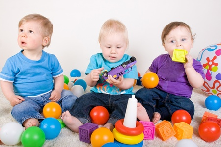 One year old babies  enjoy playing with toys. Studio Shot