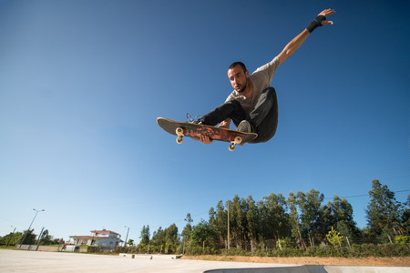 Photo pour Skateboarder flying over a ramp on blue clear sky. - image libre de droit