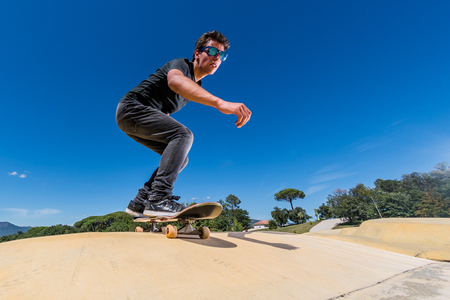 Photo for Skateboarder practice on a pump track park on a sunny summer day. - Royalty Free Image