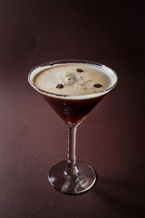 Photo pour Glass of espresso martini with coffee beans and vodka on elegant dark brown background. - image libre de droit