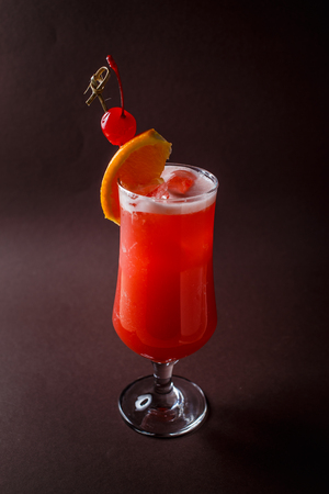 Photo pour Glass of red alcohol cocktail with cherry and slice of orange on elegant dark brown background. - image libre de droit