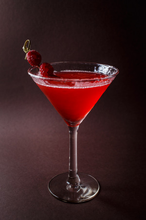 Photo pour Glass of red cocktail with paspberries on elegant dark brown background. - image libre de droit