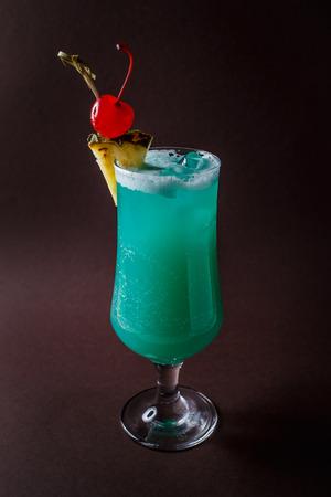 Foto de Glass of blue coctail with cherry and slice of pineapple on elegant dark brown background. - Imagen libre de derechos