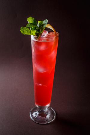 Foto de Glass of red alcohol cocktail with mint and orange on elegant dark brown background. - Imagen libre de derechos