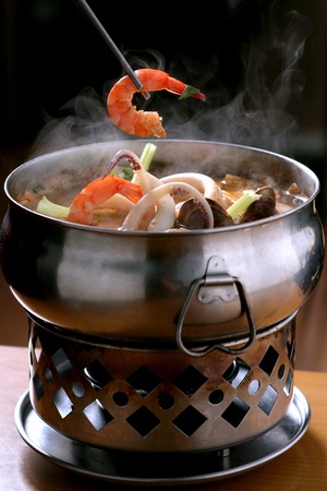 Photo for Traditional Chinese seafood hot pot with a shrimp held in a pair of chopsticks - Royalty Free Image