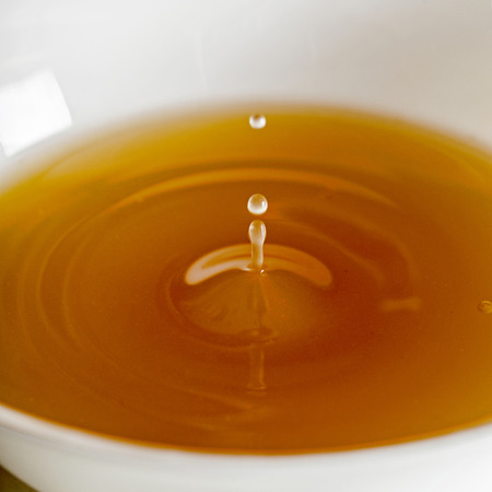 Foto de Water drop falling into a broth, clear soup in a white cup - Imagen libre de derechos
