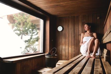 Foto per A beautiful woman wearing a white towel takes a sauna: The sauna is made of wood. Concept of: relax, vacation, wellness center. - Immagine Royalty Free