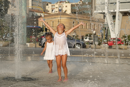 Photo pour Two little girls are having fun in a fountain, smiling in white background. - image libre de droit