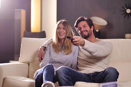Foto de A couple of lovers watching television together. Concept of: leisure, relax, tv. - Imagen libre de derechos