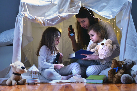 Foto de A mother with her daughters plays in the bedroom to read fairy tales in a tent built with sheets. Concept of: family, protection, educational, magic, creativity. - Imagen libre de derechos