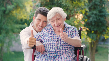 Foto per caring for the elderly, boy (man), hugging grandmother, smiling, happy, walking in the park. Concept: boarding house, sanatorium, a house for the elderly, help for the elderly. - Immagine Royalty Free