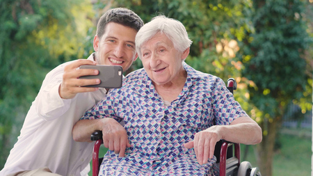Foto per Granddaughter, nurse, caring for the elderly, boy (man), hugging grandmother, smiling, happy, walking in the park. Concept: boarding house, sanatorium, a house for the elderly, help for the elderly. - Immagine Royalty Free