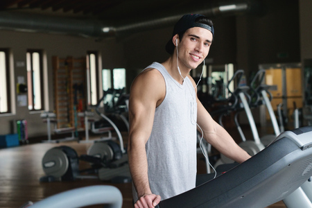 Foto per With a lot of energy on a treadmill. Concept of: sport, gym, muscles and fitness - Immagine Royalty Free