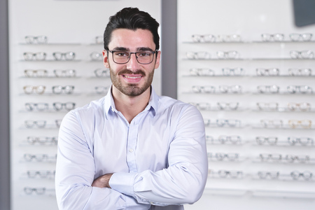 Foto per An attractive woman in an optical center smiling while watching the camera happy with the ophthalmologist's visit and the eyeglasses just bought. - Immagine Royalty Free