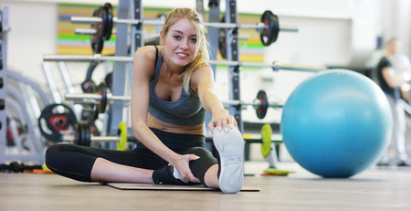 Foto per A young beautiful girl in a gym, leaning on her hands, shakes the press, making long steps, bending her knees. Concept: to love sports, to attend a gym, proper nutrition, a slender body, to be healthy - Immagine Royalty Free