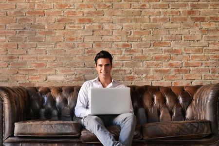 Photo for A guy on the sofa of his loft, works or studies at the computer by sending work mails or working on a design project. Concept of: work, technology, design and university student. - Royalty Free Image