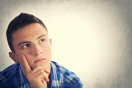 Foto de Portrait of handsome teenage boy thinking and looking up to empty space. Grunge background - Imagen libre de derechos