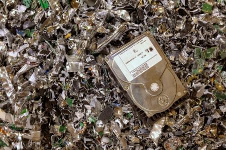 Foto de A hard drive resting on a pile of shredded hard drives - Imagen libre de derechos
