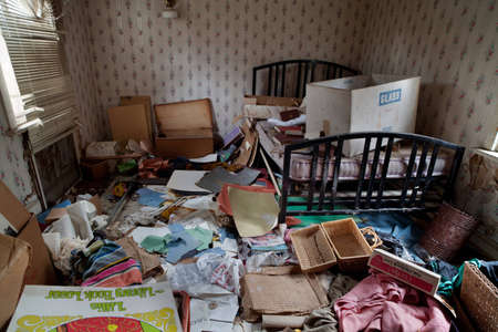 Photo for Abandoned house s bedroom completely trashed with all kind of papers, boxes and clothes lying on the floor  - Royalty Free Image