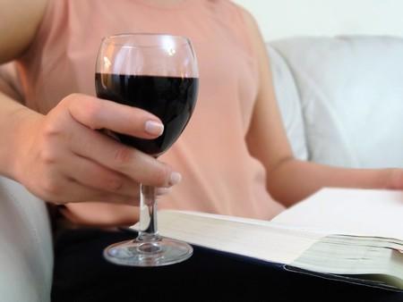 Foto de Woman reading with a glass of red wine - Imagen libre de derechos