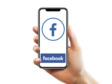 Foto de ISTANBUL - MAY 10, 2018: Apple iPhone X screen with Facebook app logo holding by a female hand against isolated white background. - Imagen libre de derechos