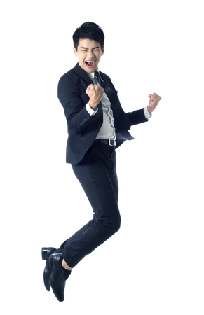 Foto de Portrait of young businessman jumping in the air and celebrating his success - Imagen libre de derechos