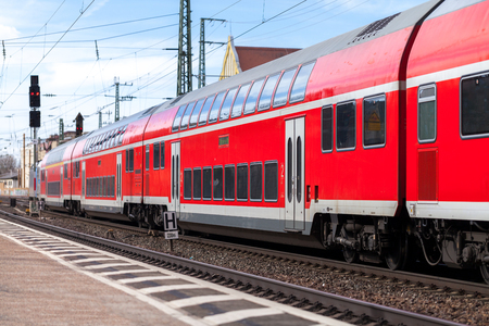 Foto per a german train passes a train station - Immagine Royalty Free