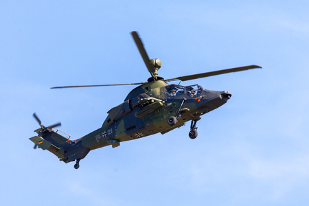 Foto de BERLIN / GERMANY - APRIL 28, 2018: Military twin-engined attack helicopter Tiger, from Airbus Helicopters flies at airport Berlin / Schoenefeld. - Imagen libre de derechos