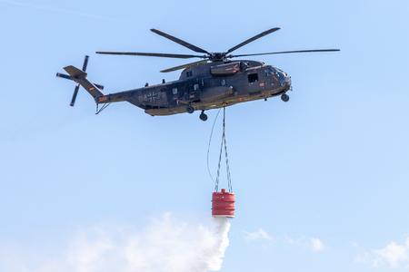 Foto de BERLIN / GERMANY - JUNE 28, 2018: Sikorsky S-65, CH-53 transport helicopter from Bundeswehr flies with a water tank in Berlin, Germany. - Imagen libre de derechos