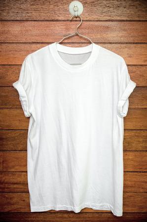 Photo pour White t-shirt hang on wood wall. - image libre de droit