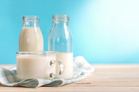 Photo pour Milk bottle and milk glass put on wooden. - image libre de droit