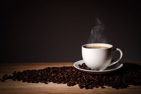 Foto per Steaming coffee in cup put on coffee beans on wood background with copy space. - Immagine Royalty Free