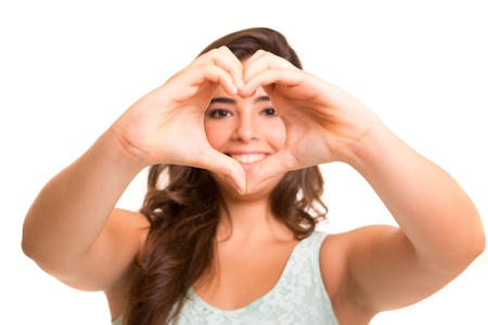 Foto de Beautiful woman making a heart shape with her hands, isolated over white background - Imagen libre de derechos