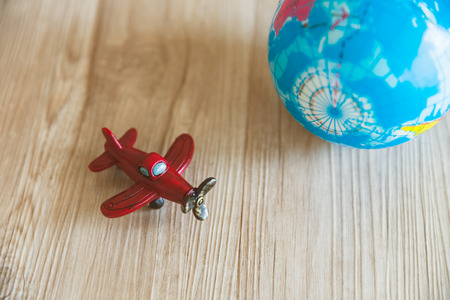 Photo pour red toy plane and globe model on wood background - image libre de droit