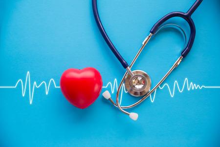 Foto de red rubber heart and stethoscope on blue background with cardiogram, health concept - Imagen libre de derechos