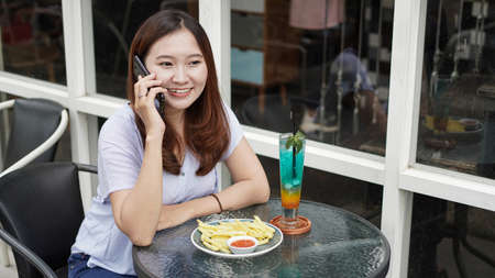 Asian business woman calling at cafe
