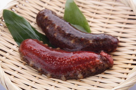 Photo pour Two raw red sea cucumber on bamboo colander - image libre de droit