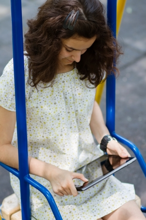 Pretty teenage girl playing with her tablet pc in the park at bright summer day