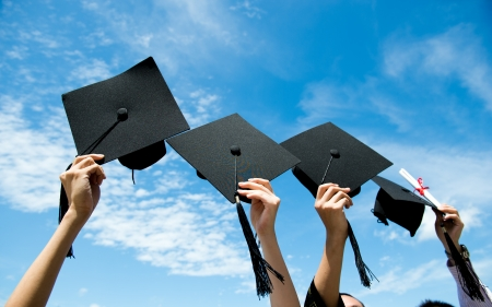 Many hand holding graduation hats on background of blue sky.