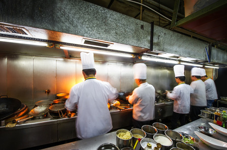 Foto de Crowded kitchen, a narrow aisle, working chef. - Imagen libre de derechos
