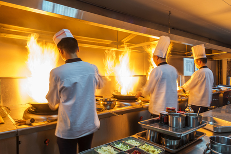 Photo pour Chef in restaurant kitchen at stove with pan, doing flambe on food - image libre de droit