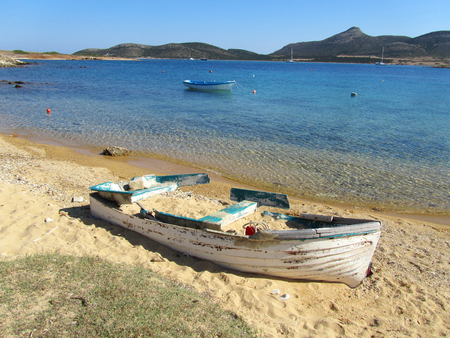 Foto de A sandy beach in Antiparos with limpid turquoise sea, an abandoned boat and a view of Despotiko island on the background. In Cyclades, Greece. - Imagen libre de derechos