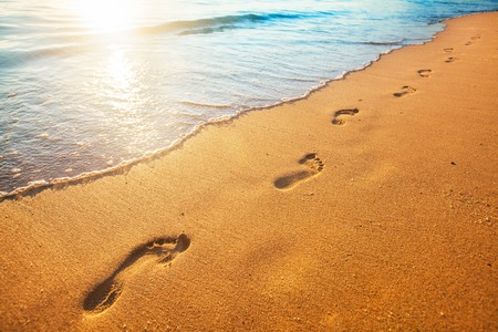Foto de beach, wave and footprints at sunset time - Imagen libre de derechos