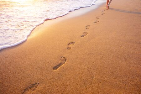 Photo pour beach, wave and footprints at sunset time - image libre de droit