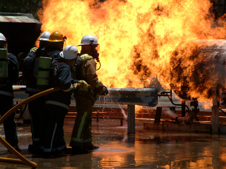 Foto de Huge Flames as gas leak catches fire and burns out of control with fire crews trying to dampen flames - Imagen libre de derechos