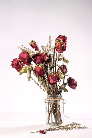 Photo pour Bouquet of red dried roses in glass vase on white background - image libre de droit