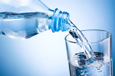 Photo pour Close-up pouring water from bottle into glass on blue background - image libre de droit